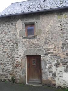 Fenêtre à meneau partiellement bouchée et encadrement de porte qui est peut-être modifié…